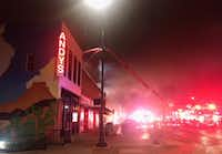 Firefighters dowse nearby buildings early Tuesday morning to keep the fire from spreading or burning down the entire east side of the downtown Square. The fire destroyed the Downtown Mini Mall, while other businesses suffered smoke and water damage.Courtesy photo