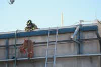 A Denton firefighter pulls a firehose to the roof of Morrison Milling Co. on Wednesday after reports of an explosion in a dust collection unit at the plant.DRC