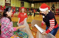 First Baptist Church elves Kim Lahart, right, and Lauri Darlington help Cecilia Hernandez, left, shop at the Elves Shelves toy giveaway on Friday.Al Key - DRC