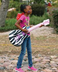 Eightyear-old Kyaisha Milton rocks out with her inflatable guitar.David Minton/DRC