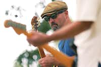 Bass and guitar necks frame the face of Brian Wilkerson as he plays on one of the stages at Quakertown Park.David Minton/DRC