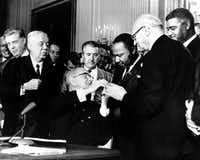 <TypographyTag1>ABOVE:</TypographyTag1> On July 2, 1964, President Lyndon B. Johnson reaches to shake hands with Martin Luther King Jr. after presenting the civil rights leader with one of the 72 pens used to sign the Civil Rights Act in Washington. <137>Surrounding the president, from left, are, Rep. Roland Libonati, D-Ill., Rep. Peter Rodino, D-N.J., Rev. King, Emanuel Celler, D-N.Y., and behind Celler is Whitney Young, executive director of the National Urban League. <137>