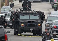 Police patrol through a neighborhood in Watertown, Mass., while searching for a suspect in the Boston Marathon bombings, Friday, April 19, 2013. The bombs that blew up seconds apart near the finish line of the Boston Marathon left the streets spattered with blood and glass, and gaping questions of who chose to attack and why.Charles Krupa - AP