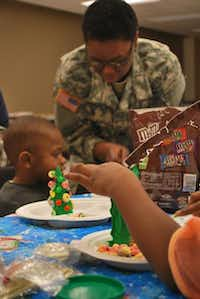 Children create Christmas treat made of ice cream cones, cereal and candy on Sunday at the Denton United States Army Reserve.John D. Harden