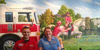 The owners of the new Flower Mound Firehouse Subs, Bryan Danilowicz and Virginia Danilowicz posed in front of the restaurant's new mural.Contributed photo - Firehouse Subs