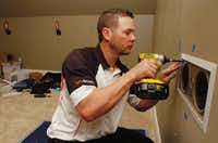 Brian Harrison, owner of Intense Home Technology, installs Proficient speakers with the home theater system being put in a home in Highland Village on Thursday.Al Key - DRC