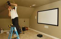 Brian Harrison, owner of Intense Home Technology, installs a 5.1 surround package with the home theater system being put in a home in Highland Village on Thursday.Al Key - DRC
