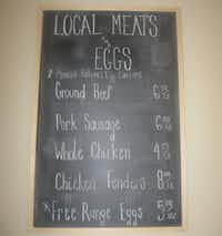 A chalkboard lists meats and eggs from area ranches.Karina Ramírez - DRC