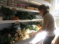 Katy Crocker organizes lettuce and other items in the refrigerated section of Earthwise Produce on Thursday.Karina Ramírez - DRC