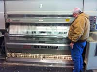 Cotton gin coop manager Larry Tomlinson inspects cotton as it goes through a cotton gin stand.Adrian O'Hanlon