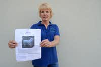 Kat Manning holds up a poster of a lost pet for whom she and her search-and-rescue dogs are on the lookout.Neighborsgo