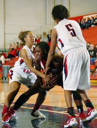 Ryan junior guard Teana Ogden (23) and junior guard Jefferyonna Holley (5) try to wrestle the ball away from Wichita Falls junior post Karlesha Clark (32), Tuesday, January 10, 2012, in Denton, Texas.DRC file photo