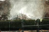 Firefighters hose down the smoldering remains after a gas explosion destroyed a building on E Main St in Lewisville Friday afternoon causing a 3-alarm fire, Friday, January 11, 2013, in Lewisville, TX.David Minton - DRC
