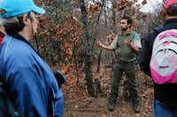 Park Ranger Rick Torres tells New Year's Day hikers about the types of minerals that can be found on branches, helping lead to the growth of fungi and mushrooms, on Sunday at the Isle du Bois Unit of Ray Roberts Lake State Park, near Pilot Point.Tomas Gonzalez - DRC