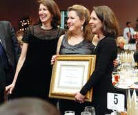 Janet Shelton, left, Denton Public School Foundation vice president of development, Vicki Sargent and Karen Goff, foundation president, stand with Sargent after she is thanked for her service at the foundation's Groundhog Day Gala on Saturday.David Minton - DRC
