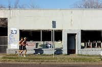Joggers run past Barney's Auto Parts, which has been on East Hickory Street for 52 years.Al Key - DRC