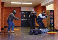 Police officers from Corinth, Hickory Creek and Lake Dallas participate in tactical training at Lake Dallas Middle School on Tuesday.Al Key - DRC