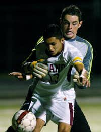 Guyer senior goalkeeper Landon Cooper (0) grabs Plano senior forward Ramon Gallegos (13) trying to block a shot, Wednesday, April 4, 2012, at Tommy Briggs Cougar Stadium in The Colony, Texas.David Minton