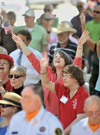 Jane Torrie raises her arms in praise as the Rev. Bruce Troy of Southmont Baptist Church says a prayer Thursday for the U.S. armed forces and veterans during the National Day of Prayer on the lawn of the Courthouse on the Square in Denton.Al Key