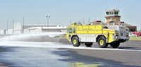 The new Airport Rescue and Firefighting Vehicle prepares to demonstrate its efficiency in extinguishing a fire at the Denton Airport during its unveiling Wednesday.Al Key