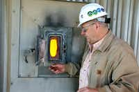 Gibbons Creek Steam Electric Station director Craig York, on the 17th story of the power plant, opens a door to show the glowing, 2,000-degree fireball inside the coal-fired boiler. The fireball is controlled by adjusting air-to-fuel mixtures, chemical conditions, oxidation of mercury and formation of carbon monoxide.Amelia Jaycen