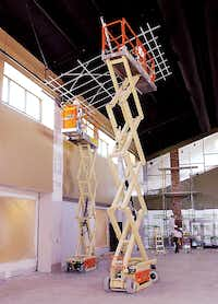 Workers employ portable lifts as they build the ceiling of the expansion to the commons area at the Liberty Christian School in Argyle Thursday August 9, 2012.Al Key