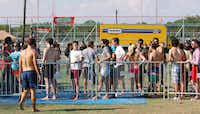 People wait in line to go on the giant inflatable water slide at the Hot Wet Mess in Denton.DRC/David Minton