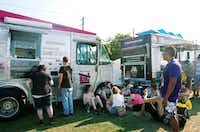 A group of fans take a break for a snack in the shade of a food truck during the Hot Wet Mess on Saturday.DRC/David Minton