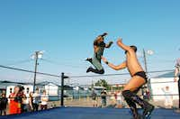 XCW wrestlers fight in a ring set up at the Hot Wet Mess on Saturday at the North Texas State Fairgrounds.DRC/David Minton