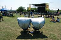 Some fans beat the heat and sun with a pair of chairs with sunshades Saturday at the North Texas State Fairgrounds.DRC/David Minton