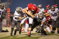 Aubrey senior running back Daniel Longhenry (22) charges through two Anna Coyotes at Chaparral Stadium on September 6, 2013.Maegan Puetz