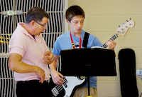 Tiger Jazz Band director Travis Harris teaches bass guitar player Chase Audirsch the technique of finding the frets and sliding his fingers down the neck of a guitar during practice at McMath Middle School.Al Key