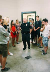 "Officer Mark Hodges, the school resource officer for Ryan High School, shows off the ""drunk tank"" cell in the city jail to foreign exchange students from Berlin on Wednesday.DRC/David Minton"