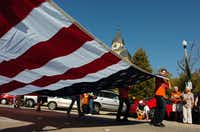 Members of Frenchy's community service volunteers carry a large American flag in the  University of North Texas homecoming parade on Saturday.DRC/David Minton