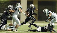 Guyer sophomore quarterback Jerrod Heard (2) hangs on to the ball and whips around the backfield against Southlake Carroll, Friday, November 4, 2011, at C.H. Collins Athletic Complex in Denton, TexasDavid Minton
