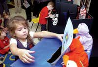 Sophie Partain, 4, casts her ballot for a class mascot and a school snack while another voter agonizes over his ballot in the voting booth at the Primrose School of Hickory Creek on Monday.Al Key