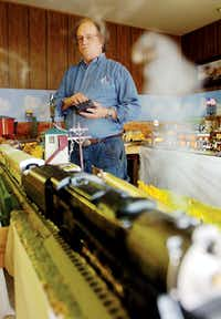 Steve Davis operates the controls of his model train exhibit Monday at his business, The Wood House, in Denton.Al Key - DRC