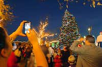 People take pictures with the Christmas tree at the Denton Holiday Lighting Festival on Friday.David Minton - DRC