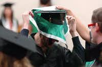 College of Visual Arts and Design student Jarrod Estes gets a little help putting a yoke on over his cap at a fall graduation ceremony Saturday at the University of North Texas.DRC - David Minton