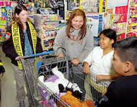 Donna Krouskup, left, a Denton Police Department crime scene investigator, helps Mayra Salazar and her children — 10-year-old Celia and 8-year-old Hector — find toys and clothes during the Shop with a Cop event at the Walmart on Loop 288 Monday morningAl Key - DRC