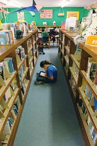 Katelyn Earle (10) disappears into a story as she reads a book in the middle of an aisle at the Krum Public Library, Tuesday, December 18, 2012, in Krum, TX.David Minton - DRC