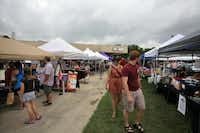 People browse vendors' tents Saturday during the Better Block project's transformation of the former Piggly Wiggly location on Sherman Drive. The weekly Denton Community Market moved to the site for the day.David Minton - DRC