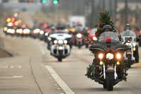 A biker with a Christmas tree decorating his ride leads a group down Teasley Lane as they ride to Cumberland Presbyterian Children's Home on Saturday.David Minton