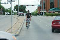 A cyclist wearing headphones rides the wrong way down the northbound lanes of Carroll Boulevard near the intersection with Hickory Street as oncoming traffic turns onto Carroll. More than half of all accidents in Denton County involving a vehicle and either a pedestrian or bicycle happen within the Denton city limits.David Minton - DRC