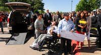 Jose Bravo holds a check for $25,000 dollars to help care for his son, Brian. The family was also given a wheelchair-accessible van to help transport Brian after he graduates from high school in June.Barron Ludlum