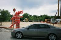 Conezilla — a sculpture made from orange traffic barrels, safety cones and channelizer cones — warns drivers along the southbound Interstate 35E feeder road south of the Lewisville Lake bridge to slow down Tuesday in Denton.David Minton