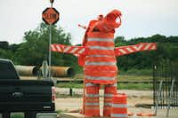 Conezilla — a sculpture made from traffic barrels, safety cones and channeliz cones — warns drivers along the southbound Interstate 35E feeder road south of the Lewisville Lake bridge to slow down in the construction area Tuesday in Denton.David Minton