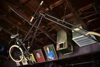"""A chopped bicycle made by Justin Sires, a.k.a. Repo, hangs in front of artwork in the rafters at Dan's Silverleaf. """"One day he rode in on that bike and I said, 'I need that,'"""" says proprietor Dan Mojica.David Minton"""