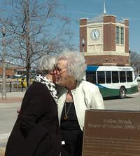 Former Mayor Euline Brock, right, gets a hug Tuesday from Margaret Chalfant of the Greater Denton Arts Council in front of the plaque unveiled during the naming ceremony at the Euline Brock Downtown Denton Transit Center.Al Key