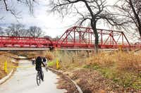 Bicyclists ride under Hickory Creek Bridge over the Elm Fork of the Trinity River along FM428 on the greenbelt Monday in Aubrey.Photos by Al Key